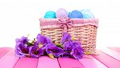 Purple artificial eustoma and woolen balls of yarn in basket isolated on white