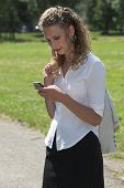 Businesswoman In The Park Sending A Text Message