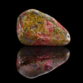 pic of feldspar  - Mineral Unakite with reflection on black surface background  - JPG