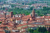 Typical italian houses with red rooftops and bell tower of the cathedral in old town of Alba, Italy.