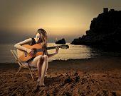 young girl playing guitar at sunset