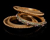 picture of bangles  - Close up of designer golden bangles having itself craft of gold looking historic over black background - JPG