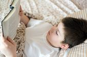 Boy Reading A Book At Bedtime Lying In Bed