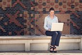Attractive Woman Working Outdoor On A Laptop