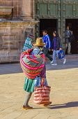 CUZCO, PERU, MAY 1, 2014: Local woman in folk attire with a Manta, which is a traditional carrying cloth, walks by Basilica Menor de la Merced