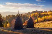 Autumn landscape with haystacks. Evening in a mountain village. Carpathian mountains, Ukraine, Europ