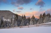 Winter landscape in the mountains. Sunny morning with beautiful clouds. Wooden fence on a mountain m