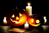Funny Halloween pumpkins and burning candles on black background