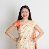 Portrait of confident Indian girl in sari smiling over grey background.