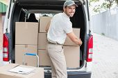 stock photo of loading dock  - Delivery driver loading his van with boxes outside the warehouse - JPG