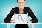 Composite image of businesswoman showing tablet pc against blue vignette