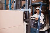 picture of forklift driver  - Forklift driver operating machine with boxes on it in a large warehouse - JPG