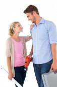 Attractive young couple holding diy tools over white background