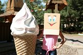 Woman with cardboard box on her head with happy face near big ice cream, outdoors