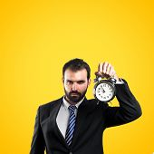 Young Businessman Holding An Antique Clock Over Yellow Background