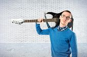 Young Man With His Guitar Over Textured Background