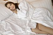 Young adult attractive and sensuality beautiful brunette woman in white bathrobe on the bed