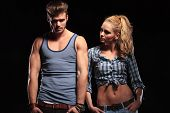 Hot blonde woman with her hands in pocket looking at her boyfriend while he is looking at the camera