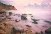 Colorful Sunset over the Sea and Rocky Coastline ,  flowing waves
