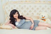 Tender Pregnant In Gray Dress On The Bed  Hugging Tummy