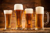 Glasses of beer with wheat ears on wooden planks