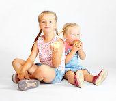 Two little girls eating fresh ripe apples.