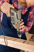 Midsection of female carpenter drilling wood in workshop