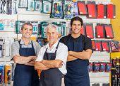 Portrait of smiling salesmen standing arms crossed in hardware shop