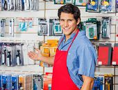 Portrait of handsome young vendor welcoming at hardware shop