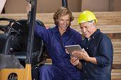 Male carpenters using digital tablet together in workshop