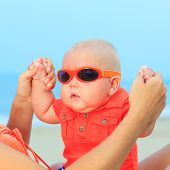 Mothers hands are holding baby wearing sunglasses