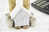 House On Pile Gold And Silver Coins With Calculator