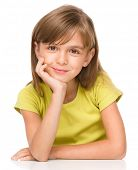 Portrait of a pensive little girl supporting her head with hand, isolated over white
