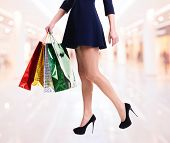 Woman in high heels with color shopping bags standing in the shop.