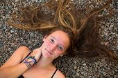 Young girl lying on the river pebbles with scattered hair. Top view.