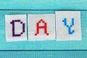 Word made embroidered letters on white fabric, on wooden background