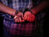 stock photo of handcuff  - Criminal hands locked in handcuffs on dark background - JPG