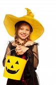 Girl in witch costume and spooky Halloween bucket