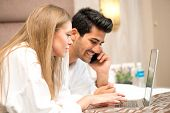 Couple in Bed using laptop and Husband talking on Phone