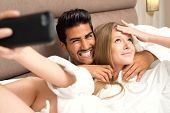 Couple in bed taking a selfie and having fun