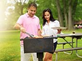 husband and wife grilling food at a park
