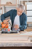 Senior male carpenter using power tool on wood in workshop