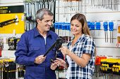 Smiling male vendor showing pliers to female customer in hardware shop