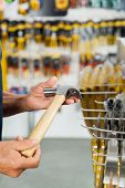 Cropped image of senior salesman holding hammer in hardware store