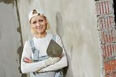 Portrait of plasterer at indoor wall renovation decoration with float and plaster