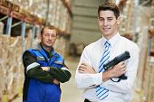smiling manager and worker in warehouse with bar code scanner
