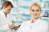 cheerful female pharmacist chemist woman portrait in pharmacy drugstore