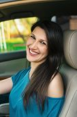 Beautiful young cheerful woman driving car