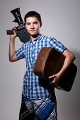 Young Man Filmmaker With Old Movie Camera And A Suitcase In His Hand