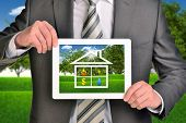 Two hands holding tablet pc with picture of house icon